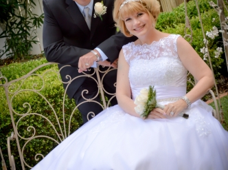 Posed wedding photography: bride and groom on bench in the chapel garden.