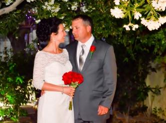 Posed wedding photography: newlyweds in chapel garden.