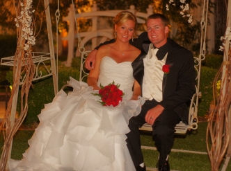 Posed wedding photography: young bride and groom on garden swing.