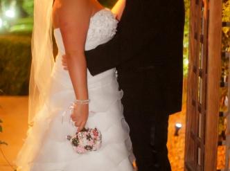 Posed wedding photography: bride and groom kiss under the Gazebo.