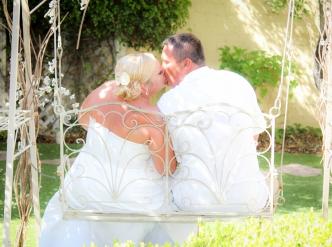 Posed wedding photography: newlyweds on garden swing.