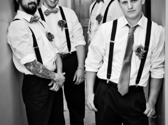 Posed wedding photography: groomsmen prepare to enter chapel in black and white.
