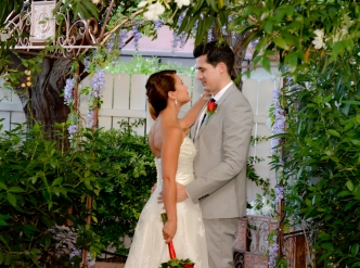 Posed wedding photography: newlywed couple by garden fence.