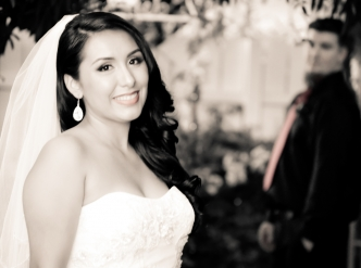 Posed wedding photography: happy bride with groom looking on from behind.