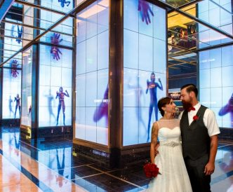 Studio Wedding Photography: upscale hotel is the backdrop for newlyweds kiss.