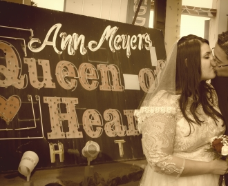 Studio Wedding Photography: couple kiss by Queen of Heart neon sign.