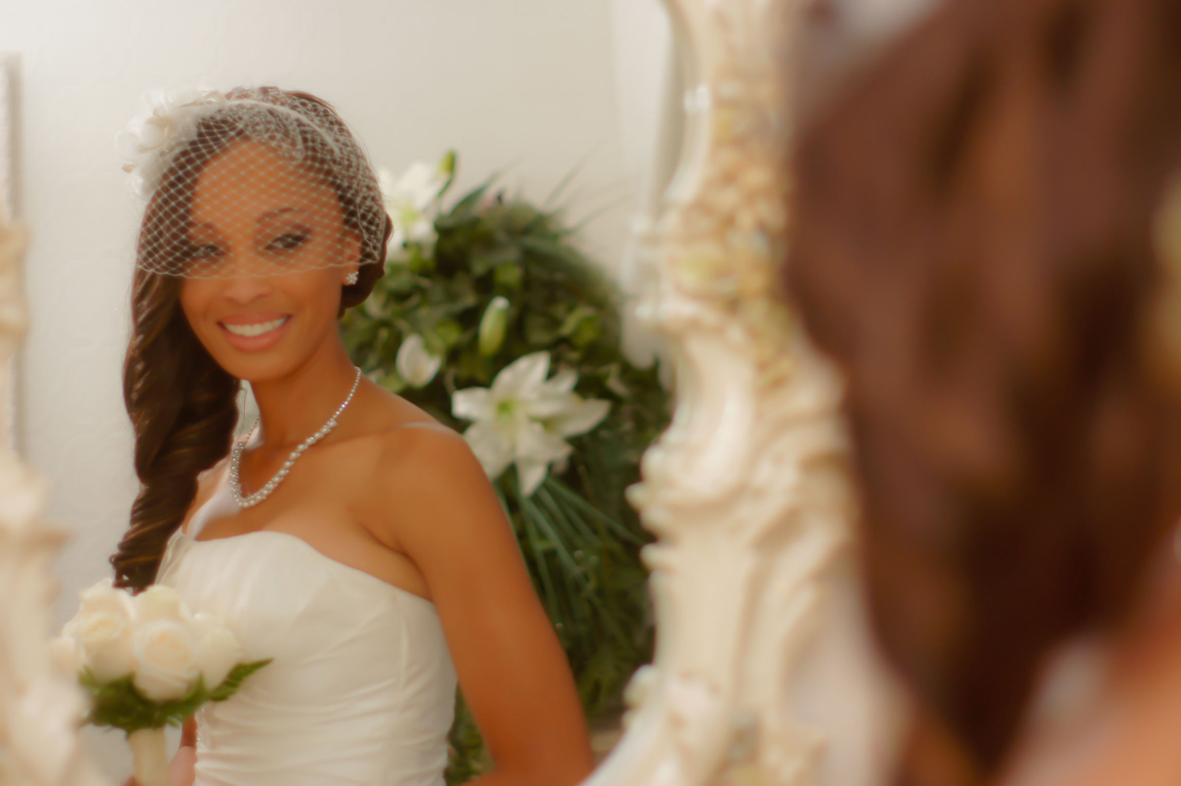 Beautiful bride in wedding dress smiles at her stunning image in the mirror.
