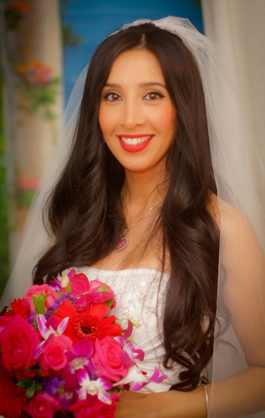 Beautiful bride with white dress and vale holds bouquet of roses and other flowers.
