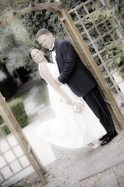 Bride and groom under trellis in chapel garden.