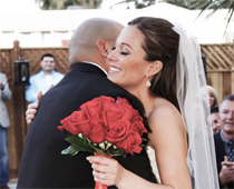 Holding a dozen red rose bouquet in hand, bride embraces her new husband.