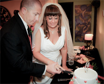 Husband and wife cut their wedding cake at wedding reception in Las Vegas.