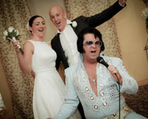 A Rhinestone Studded Las Vegas Elvis Impersonator Croons Pionately Into Microphone While An Elated Bride