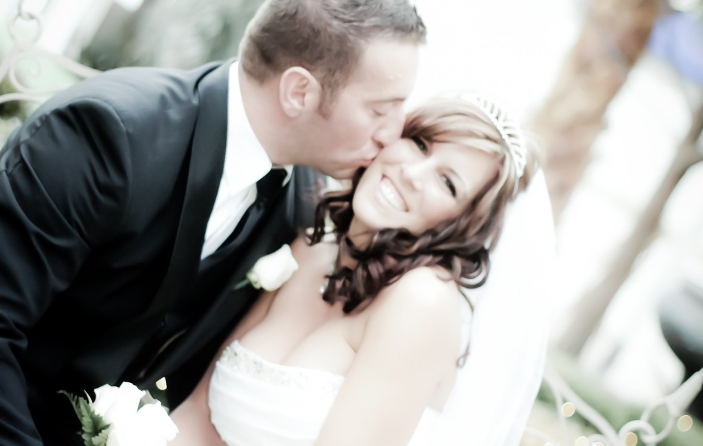 Groom kisses his bride's cheek in the garden at Mon Bel Ami Wedding Chapel in Las Vegas.