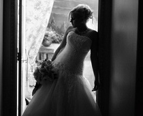 Beautiful bride in wedding dress with bouquet stands silhouette at chapel entry way.