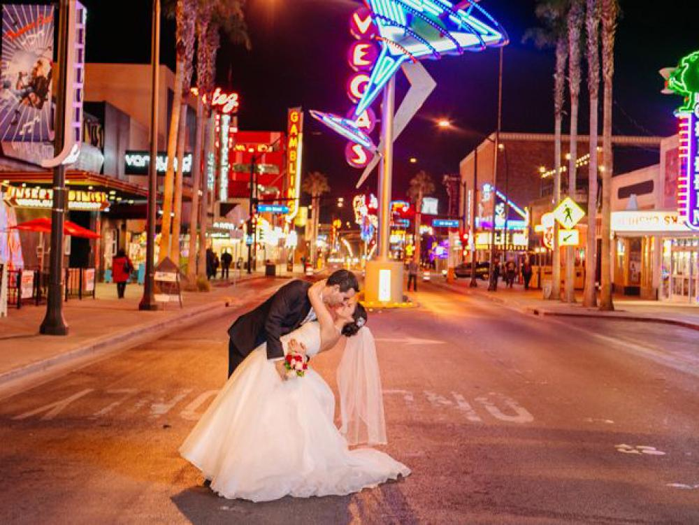 Groom dips his bride for a kiss on Fremont Street in Downtown Las Vegas.
