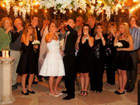 Bride, groom and a guest celebrate wedding with a toast in outdoor gazebo at Mon Bel Ami Wedding Chapel in Las Vegas.