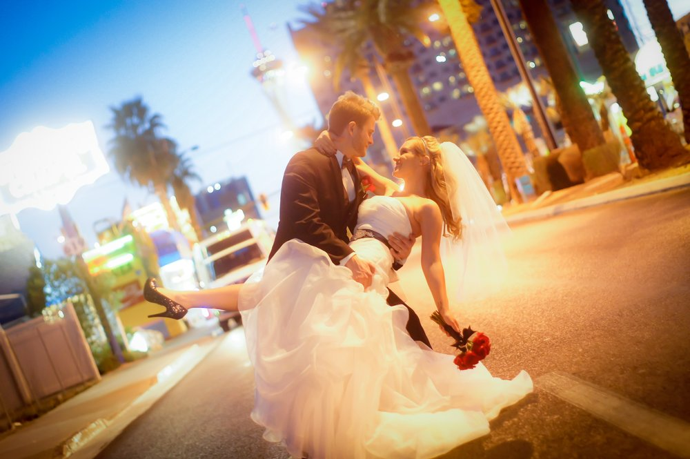 Husband dips his new wife for a kiss on Las Vegas Boulevard in front of Mon Bel Ami Wedding Chapel after their wedding.