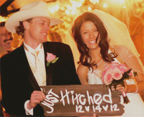 Bride and groom smile while holding a sign that says