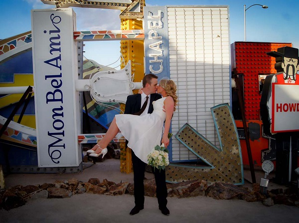 Bride and groom kiss in the Neon Boneyard Museum, Las Vegas.