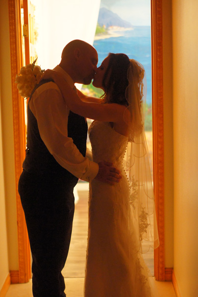Bride and groom kiss in colorful silhouette at wedding chapel.