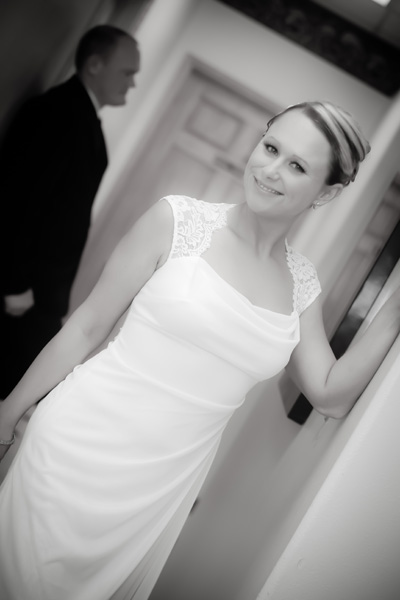 Bride poses for photo in the hallway of wedding chapel with groom standing subtly in the background.