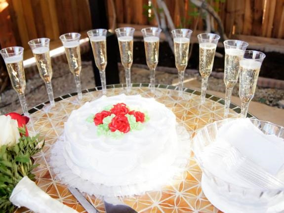 White wedding cake with green and red leaf trim sits atop reception table in front of ten glasses of champagne ready for bride, groom and guests.