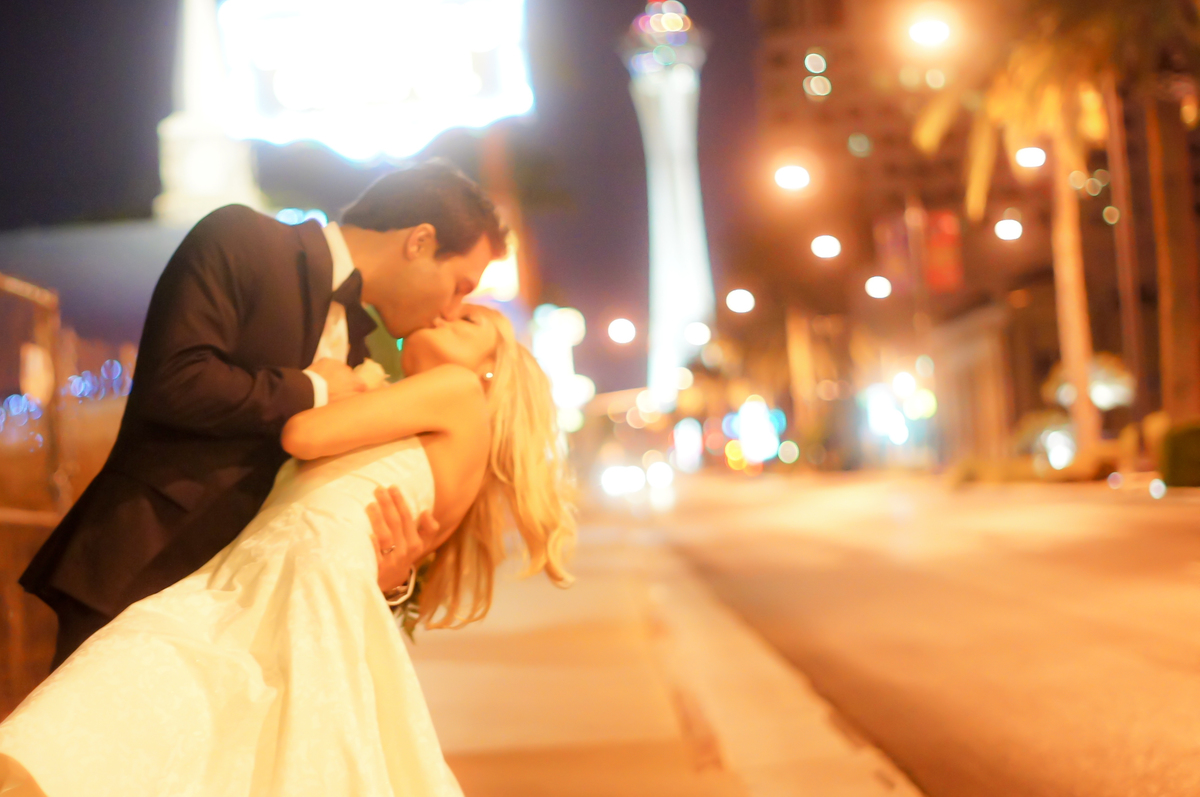 Groom dips his bride for a kiss outside on the Las Vegas Strip in fron of Mon Bel Ami Wedding Chapel .
