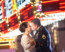 Newlyweds kiss beneath the brightly colored neon lights of Fremont St. in Downtown Las Vegas.