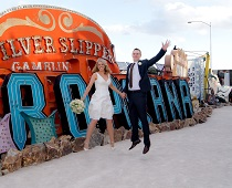 Bride and Groom leap in the air happily in front of the old Tropicana Hotel & Casino sign.
