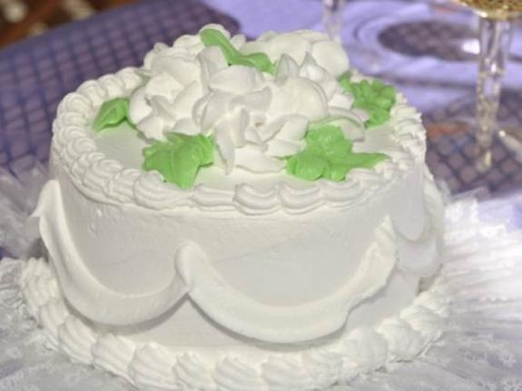 White wedding cake with green leave trim sit atop reception table.