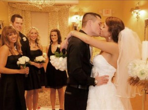 Bride and groom first kiss as married couple while bridal party looks on in wedding chapel.