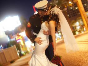 Marine in uniform dips his bride in wedding dress for a kiss on the Las Vegas Strip.