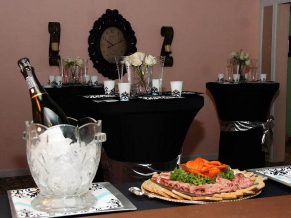Bottle of champagne on ice next to rolled meat and crackers at wedding reception.