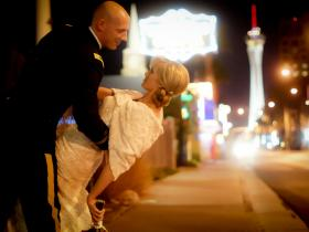 Military bride and groom dip for a kiss on Las Vegas Strip.