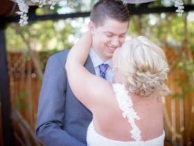 Bride and groom take their first kiss as married couple in gazebo.