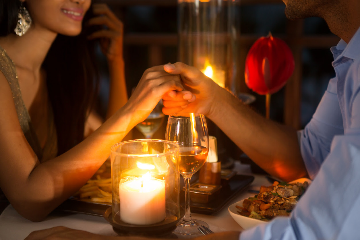 Romantic couple holding hands together over candlelight during romantic dinner.